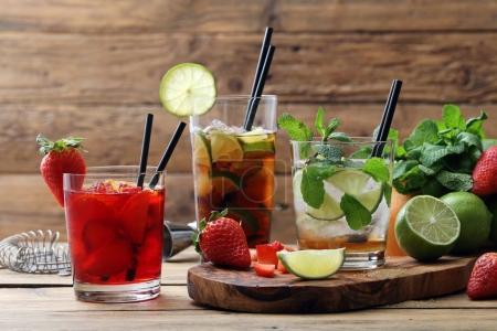 Photo pour Limonades sucrés servis avec des pailles sur la planche à découper en bois et table - image libre de droit