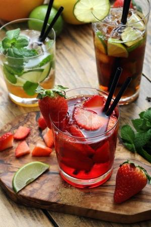 Closeup view of sweet lemonades served with straws on wooden table and chopping board.