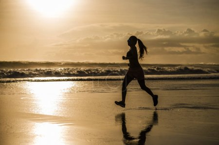 Photo for Silhouette of young Asian sport runner woman in running workout training at sunset beach with orange sunlight reflection on the sea water in healthy lifestyle and wellness activity concept - Royalty Free Image