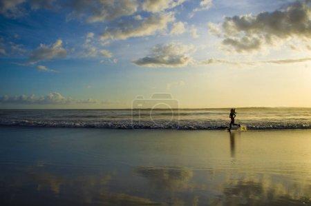 Photo pour Silhouette de jeune coureuse sportive asiatique en entraînement de course à pied à la plage du coucher du soleil avec réflexion de la lumière du soleil orange sur l'eau de mer dans un mode de vie sain et concept d'activité de bien-être - image libre de droit