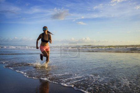 Photo for Young attractive Asian Chinese sport runner woman in running beach workout on a sunset Summer evening in beautiful sea and coast background in healthy lifestyle and fitness concept - Royalty Free Image