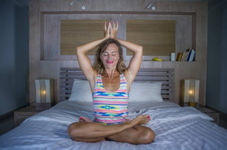 Photo for Indoors portrait of beautiful and fit healthy woman 30s practicing yoga in bed posing calm and relaxed concentrated in meditation exercise in mind control and well being lifestyle concept - Royalty Free Image