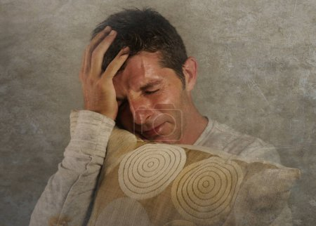 Photo for Young sad and desperate Caucasian man crying feeling lost and suffering stress and depression crying alone isolated on grunge background in dramatic face expression and emotions concept - Royalty Free Image