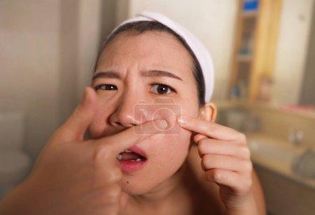 Photo pour Mode de vie gros plan visage portrait de jeune bouleversé et expressif asiatique coréen femme serrant boutons tout en regardant le miroir dans la salle de bain dans les soins de la peau du visage et concept de beauté - image libre de droit