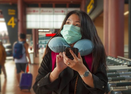 Photo for Young beautiful Asian Chinese student woman at airport wearing protective facial mask checking news and information with mobile phone on China Coronavirus epidemic outbreak - Royalty Free Image