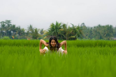 Photo pour Connexion entre l'esprit et le corps et la nature - femme chinoise asiatique séduisante et heureuse d'âge moyen en robe d'été bénéficiant d'une destination tropicale idyllique dansant gratuitement - image libre de droit