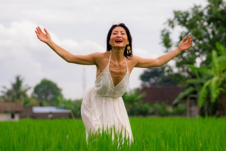 Photo for Outdoors holidays portrait of attractive and happy middle aged Asian Chinese woman in white dress enjoying freedom and nature at green field landscape carefree and playful - Royalty Free Image