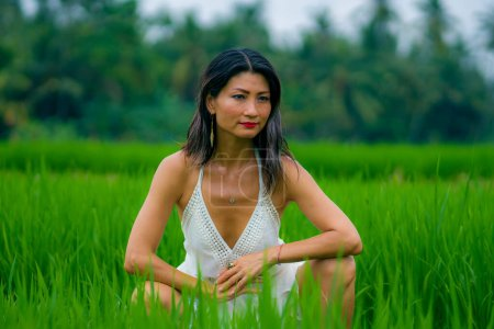 Photo for Outdoors holidays portrait of attractive and happy middle aged Asian Japanese woman in white dress enjoying freedom and nature at green field landscape carefree and cheerful - Royalty Free Image