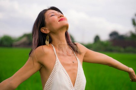 Photo for Outdoors holidays portrait of attractive and happy middle aged Asian Chinese woman in white dress enjoying freedom and nature at green field landscape carefree and cheerful - Royalty Free Image