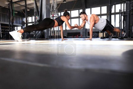Photo for Sporty couple doing plank exercise in gym - Royalty Free Image