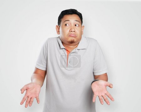 Photo for Photo image portrait of a cute young Asian man showing I don't know gesture, shoulder shrug and looking to the side - Royalty Free Image