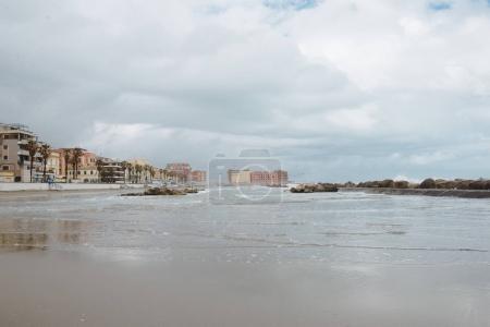 row of buildings over coastline on cloudy day, Anzio, Italy
