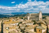 aerial view of Orvieto Cathedral and buildings with mountains on background in Orvieto, Rome suburb, Italy