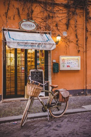 Photo for ROME, ITALY - 10 MARCH 2018: bicycle standing in front of sweets store on street of Rome - Royalty Free Image
