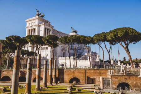 roman forum ruins with Altare della Patria (Altar of the Fatherland) building on background, Rome, Italy