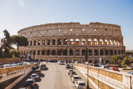 ROME, ITALY - 10 MARCH 2018: ancient Colosseum ruins on sunny day with cars parked on street
