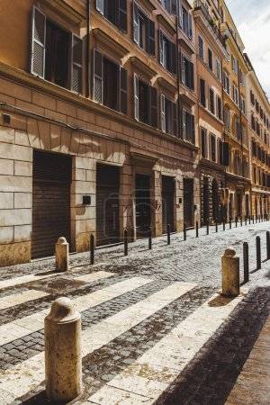 Photo for Street with ancient buildings and cobbled road on street of Rome, Italy - Royalty Free Image