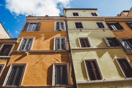bottom view of old buildings on street of Rome on sunny day, Italy