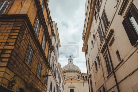 old buildings on street of Rome with cathedral on background, Italy