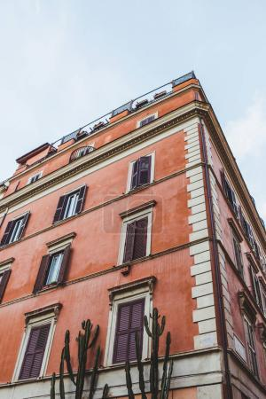 bottom view of old building on street of Rome on cloudy day, Italy