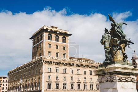 scenic shot of beautiful Palazzo Venezia from Piazza Venezia (Venezia Square) with bronze statue on foreground, Rome, Italy
