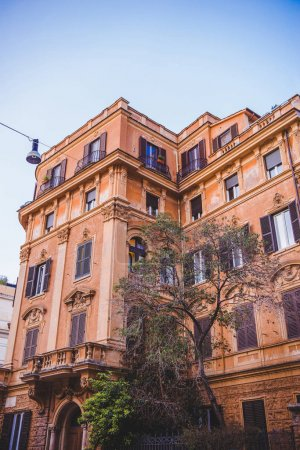 bottom view of beautiful building with tree on street in Rome, Italy