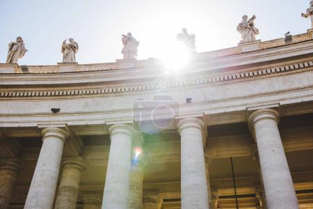 bottom view of statues with sunlight at St Peters Square in Vatican, Italy