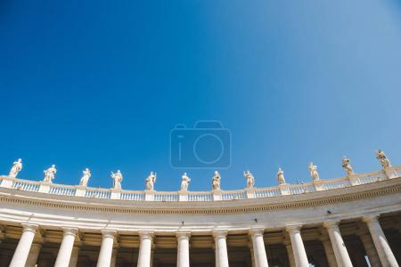 bottom view of statues at St Peters Square on blue sky in Vatican, Italy
