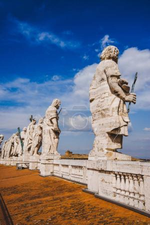 statues on top of St Peters Basilica on blue sky, Vatican city, Italy