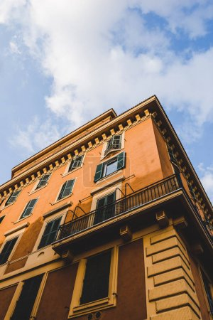 bottom view of orange building and cloudy sky in Rome, Italy