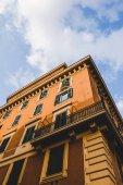 """Постер, картина, фотообои """"вид снизу оранжевый здания и пасмурное небо в Риме, Италия"""""""