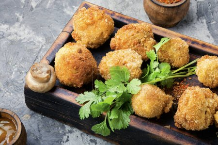 Photo for Breaded mushrooms or deep-fried mushrooms on cutting board - Royalty Free Image