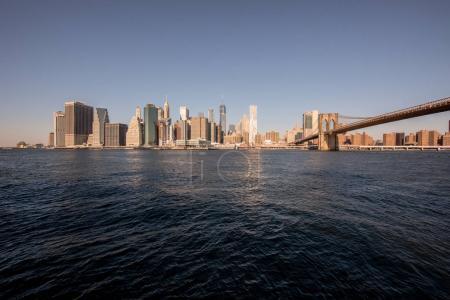 Brooklyn Bridge and Lower Manhattan skyline panorama from Brooklyn Bridge Park riverbank, New York City, USA.