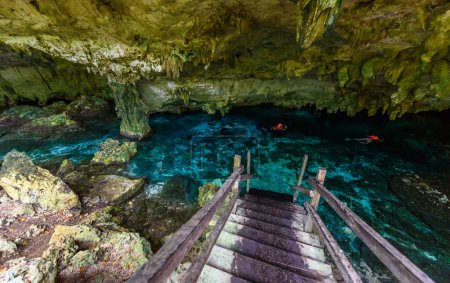 Cenote Dos Ojos in Quintana Roo, Mexico. People swimming and snorkeling in clear water. This cenote is located close to Tulum in Yucatan peninsula, Mexico.