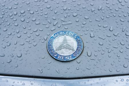 Hood emblem of Mercedes-Benz in raindrops on the gray background.