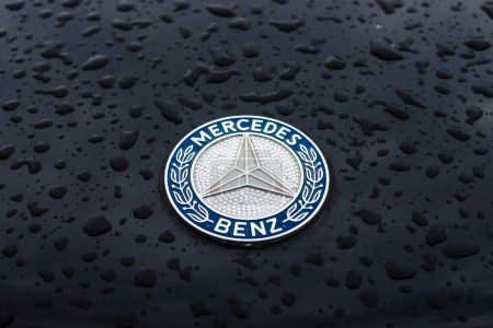 Hood emblem of Mercedes-Benz in raindrops on the dark background.