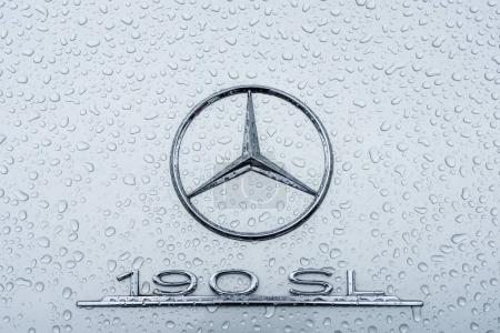Emblem of a sports car Mercedes-Benz 190SL in raindrops.