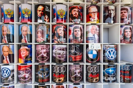 Background of souvenir mugs with images of various politicians, actors or car brands.
