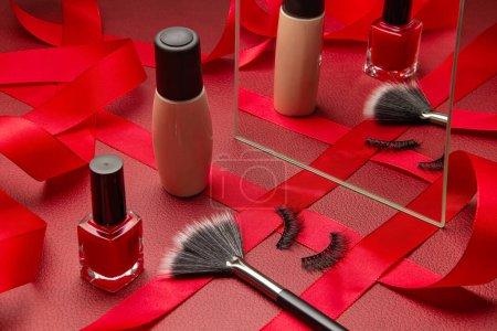 Photo pour Maquillage féminin festif avec fondation, cils, brosse à maquillage et vernis à ongles rouge avec miroir et ruban sur fond de cuir rouge. Préparation à une fête, concept de cadeaux de Noël - image libre de droit