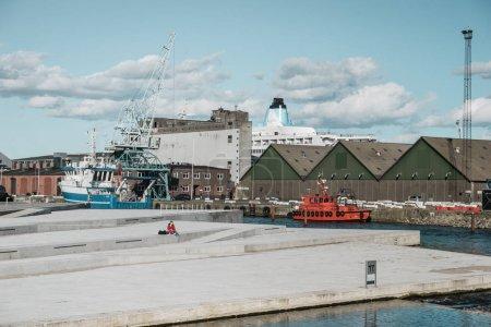 Cargo ship near crane in sea port with docks
