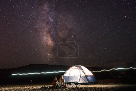 Lovely couple sitting near tent in night over dark sky with stars