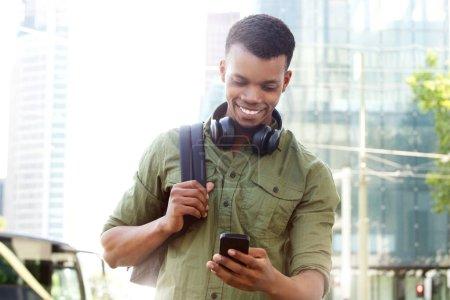 Foto de Retrato de hombre guapo con teléfonos inteligentes en ciudad sonriendo - Imagen libre de derechos