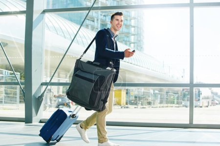 Man in station with suitcase and phone