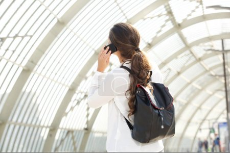 Woman with backpack talking on cellphone