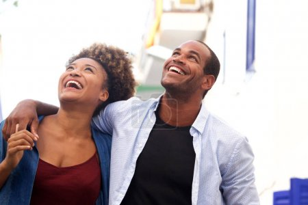 Side portrait of laughing couple walking together in embrace on date
