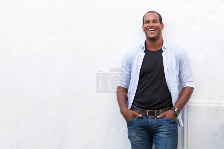Photo for Portrait of attractive man standing and laughing on white background - Royalty Free Image