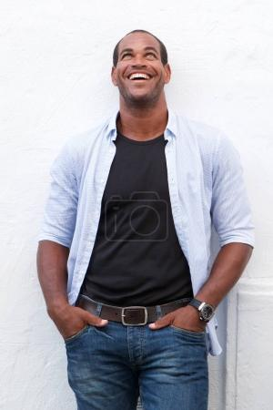Photo for Portrait of handsome man standing and laughing on white background - Royalty Free Image