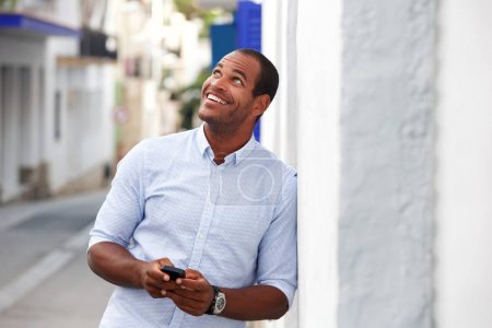 Portrait of happy man standing outside on street with mobile phone