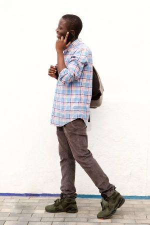 Full body side portrait of african young man walking outside with bag and cell phone