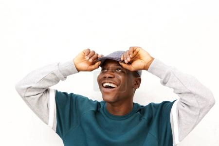 Close up portrait of cheerful young african guy with cap standing on white background
